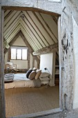 Comfortable double bed on floor below steep, exposed roof structure of half-timbered house