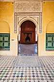 Tiled floor in yellow-painted courtyard of Moroccan house with view of open fireplace through Oriental arch