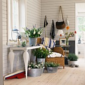 Various plants and bouquets in zinc containers, wicker chair and console table in white, wood-panelled country house