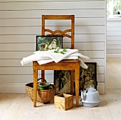 Romantic painting and table linen on antique wooden chair against white, wood-panelled partition wall