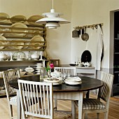 Round dining table, kitchen chairs with seat cushions and 50s, Danish designer lamp; plate rack in background