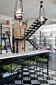 Barhocker aus schmiedeeisernem Gestell und grüne Sitzpolster vor Frühstücksbar unter Vintage Pertoleum Hängeleuchten, im Hintergrund Treppenaufgang in offenem Wohnraum