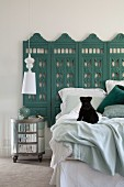 Black dog on bed against wall with antique carved screen painted petrol blue and round bedside table below pendant lamp with white lampshade