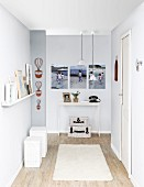 DIY renovations - grey-painted hallway, set of white stools to one side below floating shelf and delicate console table in background below gallery of photos
