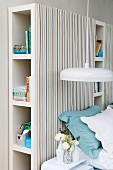 Pendant lamp with white lampshade in front of shelving units with striped fabric covers used as headboard