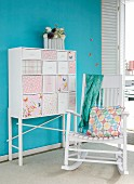 Chest of drawers with patchwork decoupage drawer fronts against blue wall and white wooden rocking chair