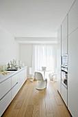Elegante weiße Designerküche mit Essplatz im Hintergrund