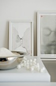 Arrangement of artworks in white picture frames leaning on white wall