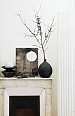 Black and white arrangement with vase and objet d'art on mantelpiece against white wall