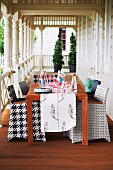 Chairs with graphic-patterned upholstery at wooden table on wooden veranda with turned pillars