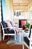 White wooden bench and armchairs with dark blue cushions around table on veranda with white balustrade and turned columns
