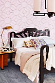Double bed with black frame against pink wallpaper with graphic pattern