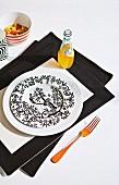 Schwarzweiss gemusterter Teller und Limonadenflasche auf schwarzweissem Tischset, an der Seite orange gefärbte Gabel