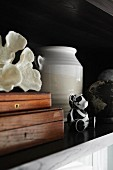 Two wooden boxes, white shell, ceramic vase and small, black and white bear ornament on shelf