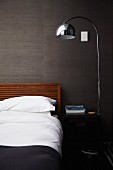 Purist double bed, shiny standard lamp and black bedside table against grey, structured wallpaper