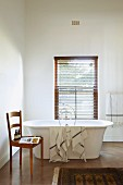 Towel draped over free-standing bathtub below window with closed louver blind, toiletries on simple wooden kitchen chair to one side