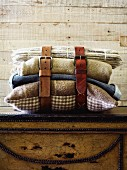 Leather belts buckled around cushions and blankets