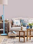 Living room in shades of brown & blue with sofa, standard lamp and wooden side tables