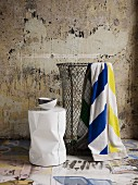 Wire laundry basket and modern stool in bathroom with tiled floor & exposed, vintage plaster