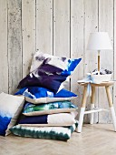 Stacked blue and white cushions next to lamp on three-legged stool