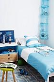 Blue teenager's bedroom with bed, bedside cabinet & storage net