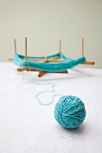Blue ball of wool spun on a wooden frame