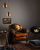 Cushion printed with portrait of man on leather armchair, copper lampshades and modern fireplace
