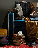 Collection of shiny fabrics and fur on armchair with blue upholstery