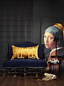 Reproduction of historical painting next to blue upholstered bench with gold velvet cushion