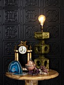 Various objects made from stone and semi-precious stone on side table against embossed wall