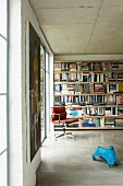 Retro office chair and child's toy in front of bookcase in purist interior with exposed concrete surfaces