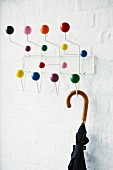 Umbrella hanging from coat rack with colourful balls on hooks