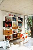 Shelving unit and designer rocking chair in purist, child's bedroom