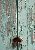 Weathered wooden door with peeling blue paint and padlock (detail)