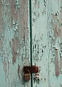 Verwitterte Holztür mit abgeblätterter blauer Farbe und Vorhängeschloss (Ausschnitt)
