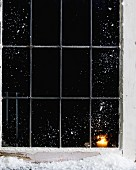 Candle burning in snow covered house window