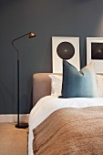 Simple bedroom with dark walls, bed, standard lamp & pictures on wall