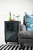 Side table with glass door on castors next to grey armchair
