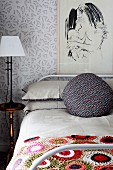 Bedroom with crocheted bedspread on bed, abstract picture on wall & bedside lamp