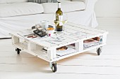 DIY coffee table made from euro pallets on castors and couch on white wooden floor