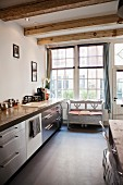 Kitchen counter with stainless steel fronts and rustic bench below lattice window