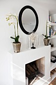 White potted orchids and ornament under glass cover on mantelpiece below round mirror with black frame on wall