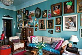 Various framed pictures of women on turquoise wall in crammed, vintage-style period apartment