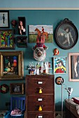 Hotchpotch of framed pictures and flea market finds on turquoise living room wall