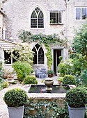 Planted courtyard of Gothic country house with box bushes around fountain