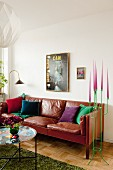 Side table with colourful tray in front of brown leather sofa next to green metal candelabra with pink candles in corner of living room