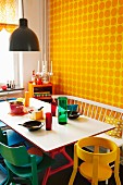Colourful painted chairs and white bench at dining table against yellow, polka-dot wallpaper
