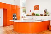 Bright orange designer kitchen with white Corian top on wide, curved worksurface