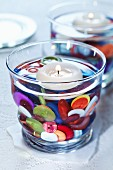 Colourful buttons as decoration in water-filled candle lantern with floating candle