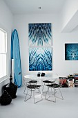 Classic wire-framed chairs around Tulip table in dining room; artworks with water motifs on wall and surfboard